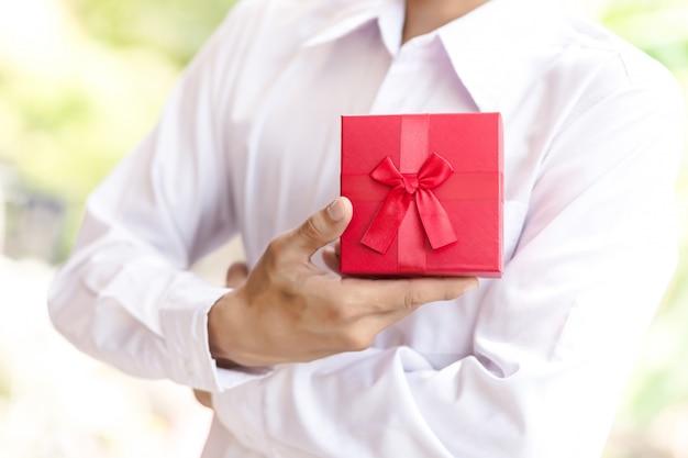 Hombre de negocios mantenga caja de regalo roja en las manos.