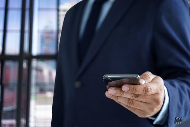 Hombre de negocios mantenga el teléfono inteligente en la calle