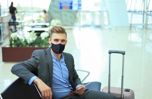 Hombre de negocios en máscara protectora con maleta en el pasillo del aeropuerto. aeropuerto en la epidemia de coronavirus.