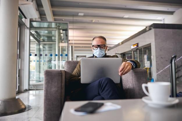 Hombre de negocios en una mascarilla trabajando en su computadora portátil