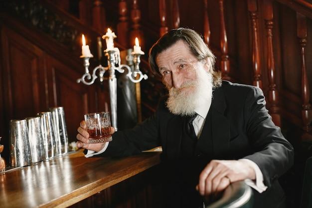 Hombre de negocios mayor barbudo. el hombre bebe un whisky. senior en traje negro.