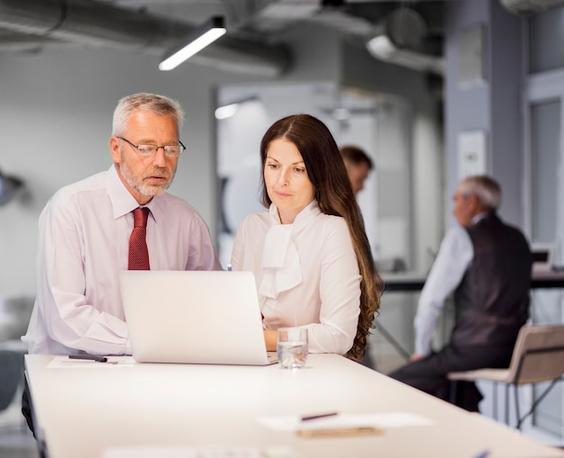 Hombre de negocios mayor y empresaria que miran el ordenador portátil en la oficina