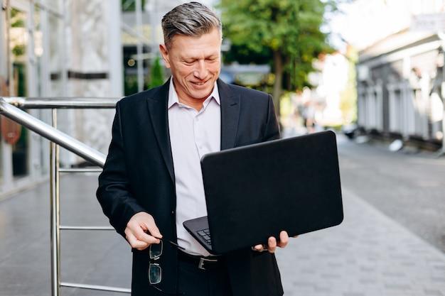 Hombre de negocios mayor feliz que sostiene el ordenador portátil en su mano en la ciudad al aire libre y que mira la pantalla.