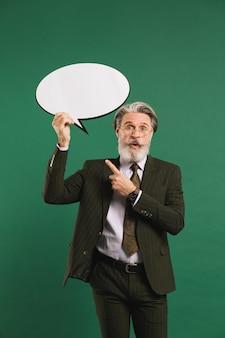 Hombre de negocios de mediana edad con barba en traje con emoji con espacio de copia en una pared verde