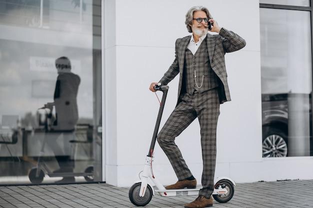 Hombre de negocios de mediana edad montando scooter en un elegante traje
