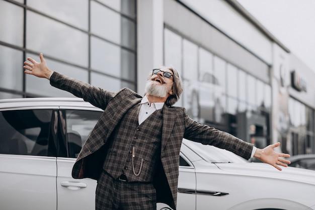 Hombre de negocios de mediana edad en un salón de autos