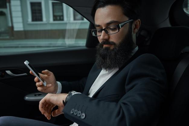Un hombre de negocios mientras viaja en automóvil en el asiento trasero con un teléfono inteligente