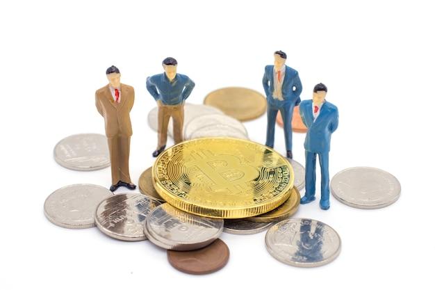 Hombre de negocios miniatura y bitcoin en el fondo blanco