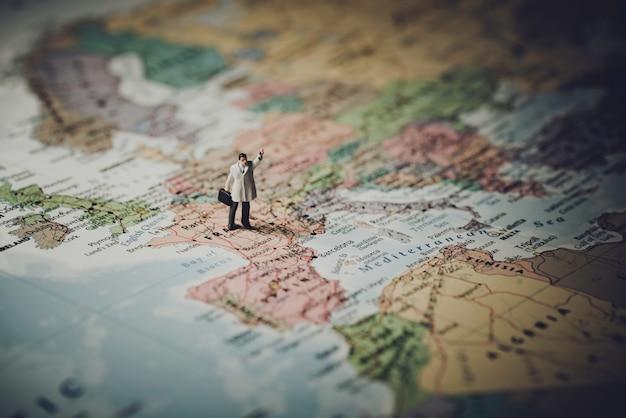 Hombre de negocios en miniatura en el mapa de europa