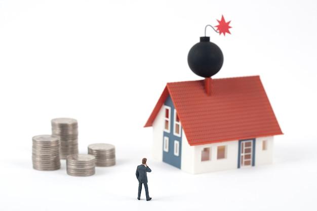 Hombre de negocios en miniatura y monedas con bomba en el techo de la casa modelo