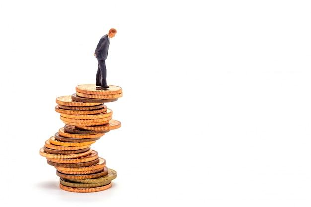 Hombre de negocios miniatura en pila en el mercado empresarial blanco de la incertidumbre.