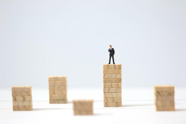 Hombre de negocios en miniatura que toma la decisión sobre las pilas de madera más altas.