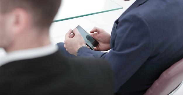 Hombre de negocios mirando la pantalla del teléfono inteligente de cerca