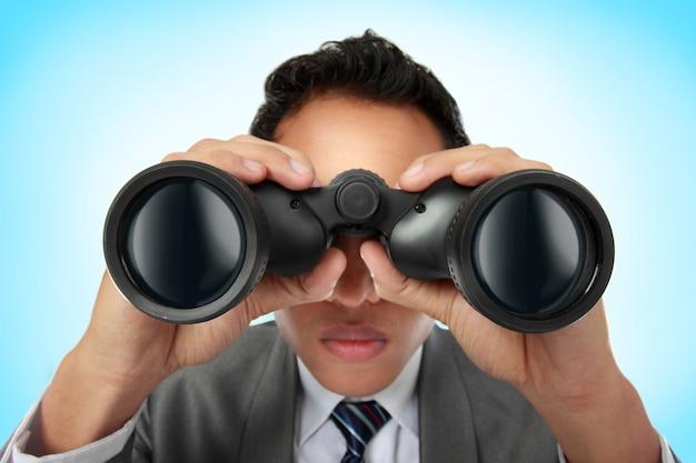 Hombre de negocios mirando a través de binoculares
