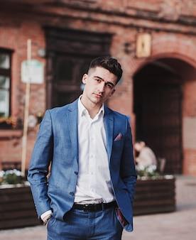 Hombre de negocios moderno. hombre joven confiado en traje de pie al aire libre con paisaje urbano