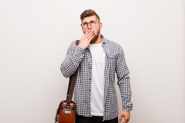 Hombre de negocios moderno joven que bosteza mostrando un gesto cansado que cubre la boca con la mano.