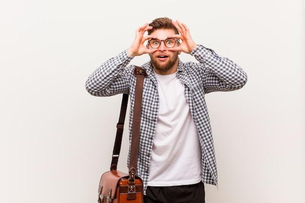 Hombre de negocios moderno joven que mantiene los ojos abiertos para encontrar una oportunidad de éxito.