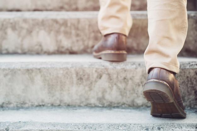 Hombre de negocios moderno que trabaja las piernas del primer que caminan encima de las escaleras en ciudad moderna.