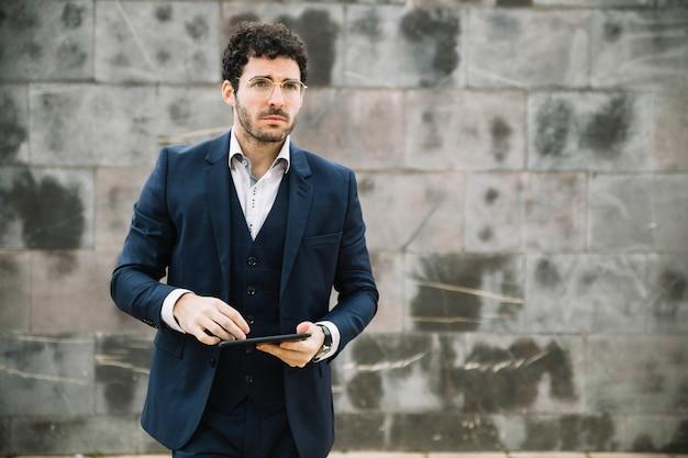 Hombre de negocios moderno usando tableta enfrente de muro