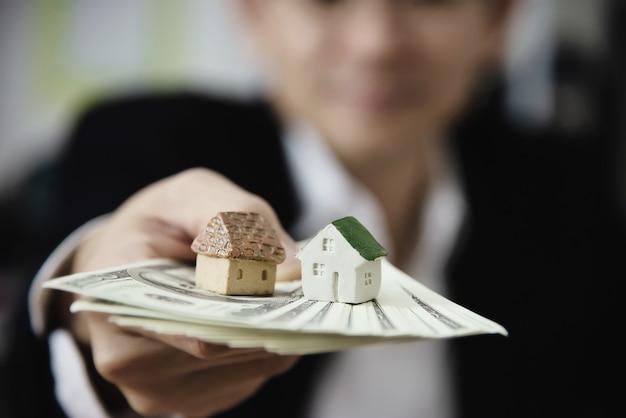 El hombre de negocios muestra dinero el billete de banco hace que el plan financiero invite a la gente a vender o comprar una casa y un automóvil - concepto de seguro de crédito de préstamo de propiedades monetarias