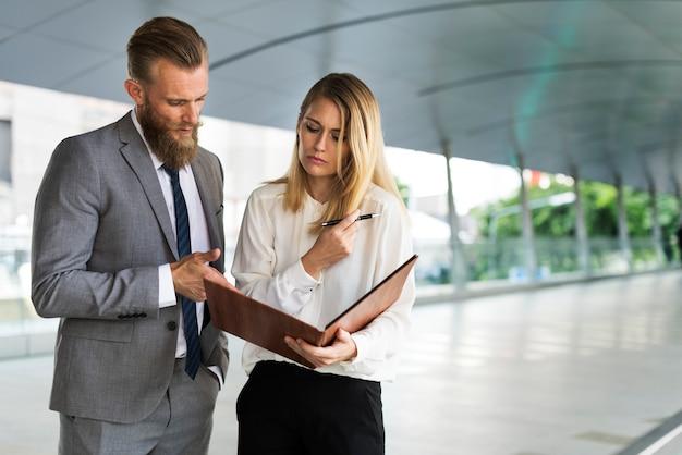 Un hombre de negocios y una mujer de negocios hablando y mirando un cuaderno.