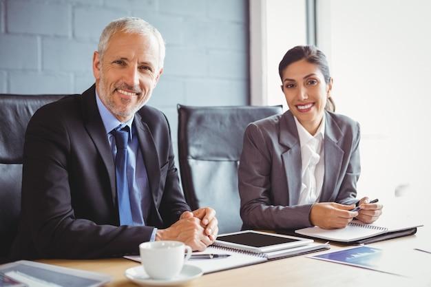 Hombre de negocios y mujer de negocios sentado en la sala de conferencias