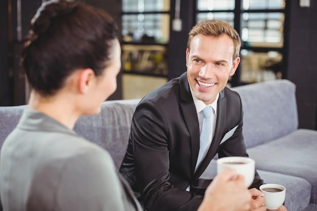Hombre de negocios y mujer de negocios tomando té durante el recreo