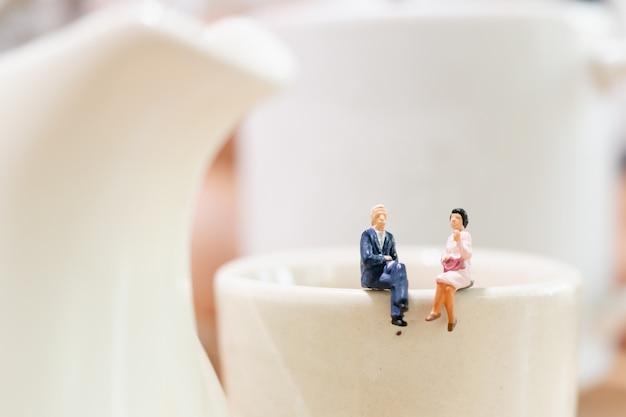 Hombre de negocios y mujer sentada en una taza de té