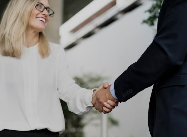 Hombre de negocios y mujeres de negocios que sacuden las manos de acuerdo