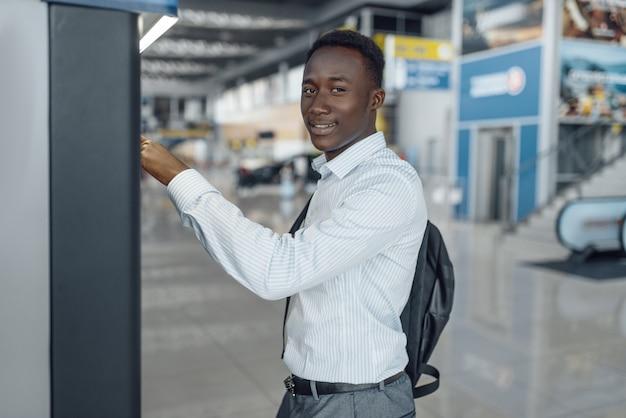 Hombre de negocios negro en la máquina de café en el concesionario de automóviles. hombre de negocios exitoso en el salón del automóvil, hombre negro en ropa formal