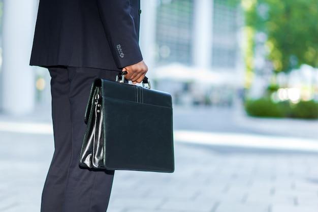 Hombre de negocios negro que lleva un maletín