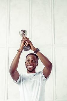 Hombre de negocios negro con trofeo.