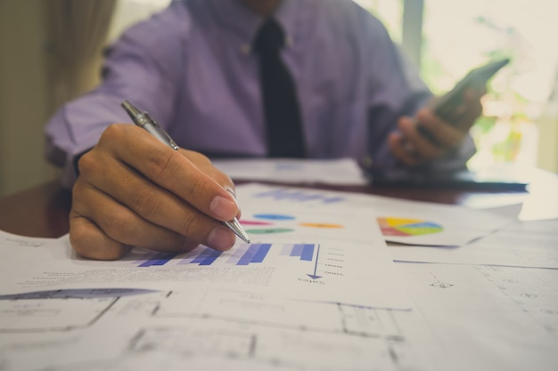 Hombre de negocios o contador que trabaja en la calculadora para calcular concepto de datos comerciales.