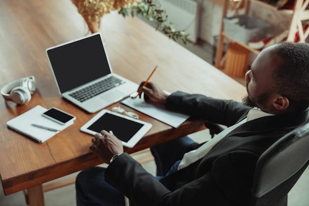 Hombre de negocios o estudiante que trabaja desde casa mientras está aislado o mantiene en cuarentena el coronavirus covid-19