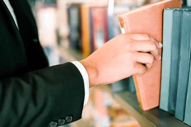 Hombre de negocios o estudiante sosteniendo un libro en la mano o eligiendo un libro en la estantería en el fondo de estanterías de la biblioteca - concepto de estudio de educación empresarial