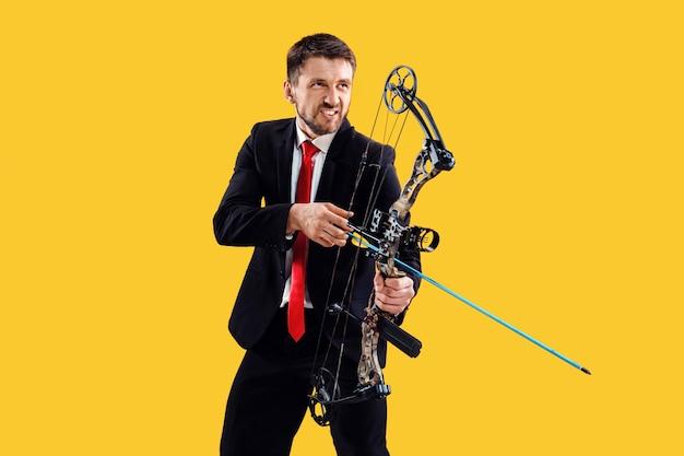 Hombre de negocios con el objetivo de objetivo con arco y flecha, aislado sobre fondo amarillo de estudio. el negocio, el objetivo, el desafío, la competencia, el concepto de logro.
