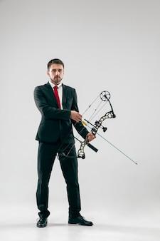 Hombre de negocios con el objetivo de objetivo con arco y flecha, aislado sobre fondo gris de estudio.