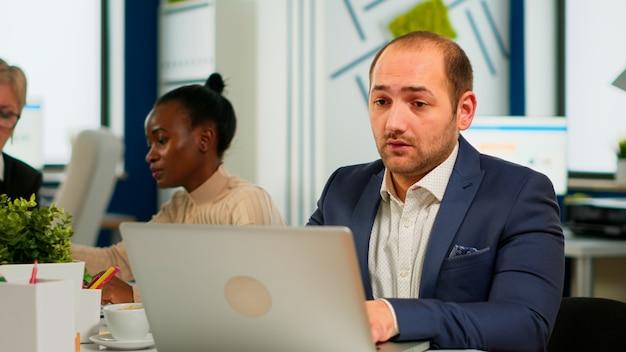 Hombre de negocios ocupado usando laptop escribiendo sentado en la mesa de conferencias en la sala amplia concentrado en el trabajo, mientras diversos colegas trabajan en segundo plano. tecnología moderna, concepto de ocupación de jóvenes.