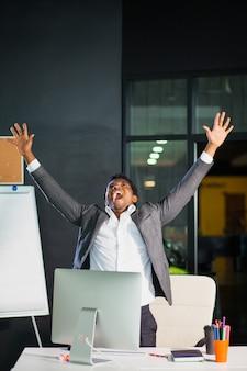 Hombre de negocios en la oficina, gesto de éxito, meta alcanzada, hombre feliz