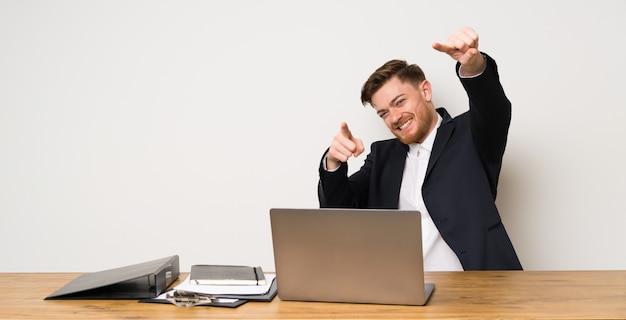 Hombre de negocios en una oficina señala con el dedo a ti mientras sonríe