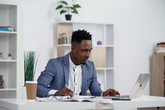 Hombre de negocios con ordenador portátil. joven empresario africano está escribiendo algo en la computadora portátil en su oficina.