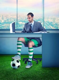 Hombre de negocios en pantalones cortos y con una pelota debajo de la mesa