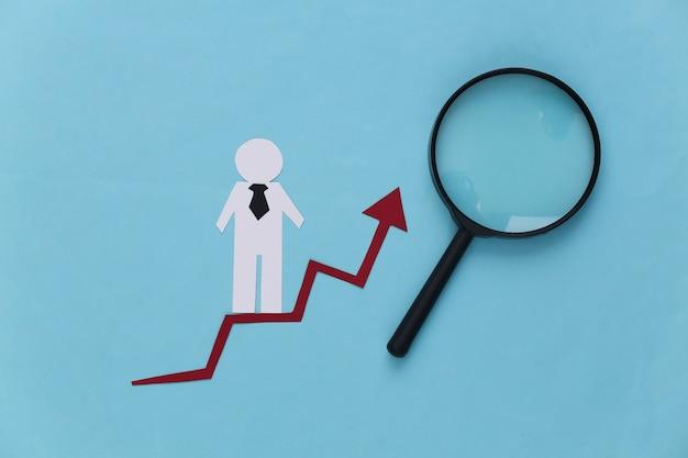 Hombre de negocios de papel en la flecha de crecimiento, lupa. azul. símbolo de éxito financiero y social, escalera al progreso