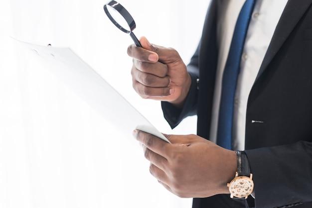 Hombre de negocios con papeles y lupa