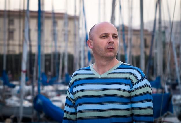 Hombre de negocios parado por veleros y yates caros en una ciudad costera