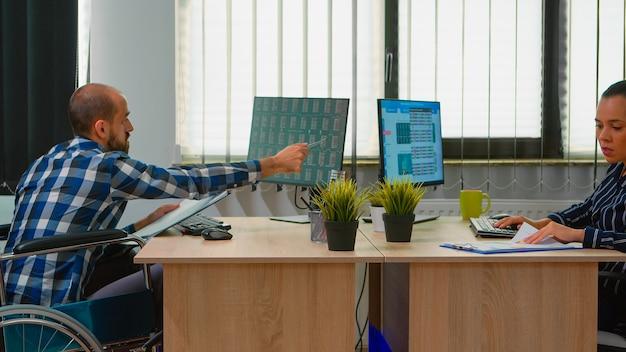 Hombre de negocios paralizado discapacitado en silla de ruedas analizando datos económicos tomando notas haciendo experiencia financiera en la oficina de negocios discutiendo con un colega. hombre inmovilizado con tecnología moderna.