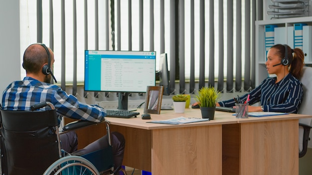 Hombre de negocios paralizado en silla de ruedas con auricular que realiza una cita a distancia y ofrece atención al cliente. freelancer discapacitado inmovilizado que trabaja en un edificio corporativo financiero utilizando tecnología moderna