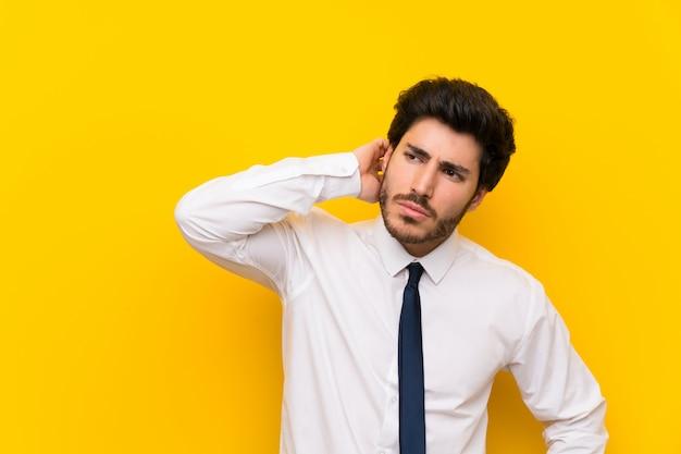 Hombre de negocios en la pared amarilla aislada que tiene dudas y con expresión de la cara confusa