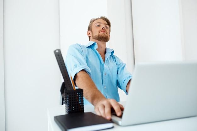 Hombre de negocios pensativo confiado hermoso joven que se sienta en la tabla que trabaja en la computadora portátil con la taza de café a un lado. interior de oficina moderno blanco