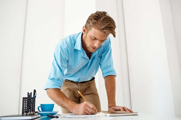 Hombre de negocios pensativo confiado hermoso joven que trabaja de pie en la escritura de la tabla en la libreta. interior de oficina moderno blanco.